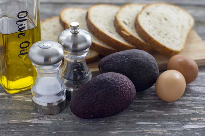 Glass bottle with olive oil, sliced bread on a bamboo cutting board, salt and pepper shakers, two whole avocados, and two brown eggs all on a wooden surface