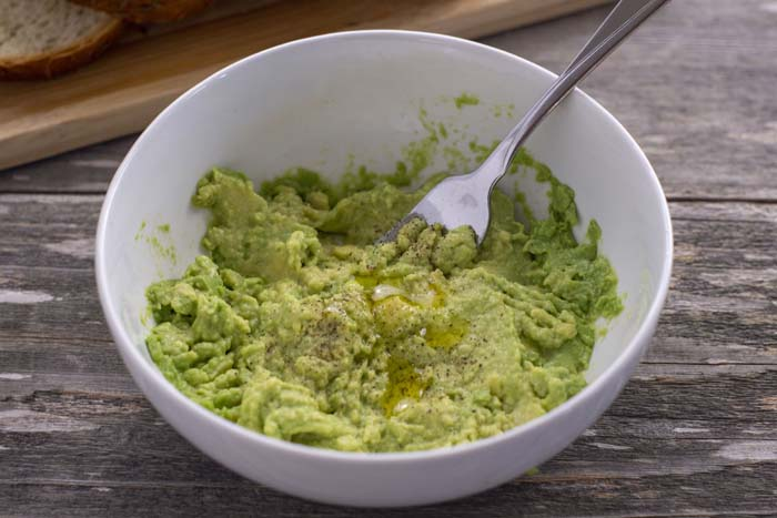 Round white bowl with smashed avocado with salt, pepper, and oil with a fork inside next to a bamboo board with sliced bread all on a wooden surface