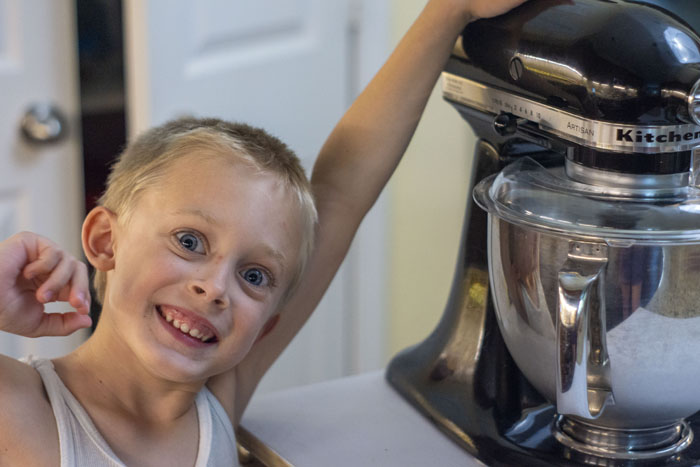 Young boy in a white shirt next to a stand mixer