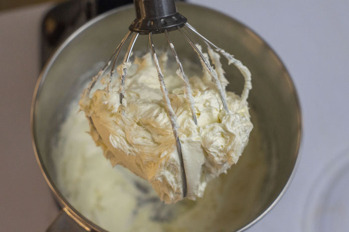 Whisk attachment on a stand mixer lifted to show whisked cream inside the mixing bowl over a white surface