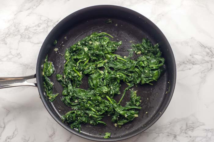 Skillet with wilted spinach and garlic over a white and grey marble surface
