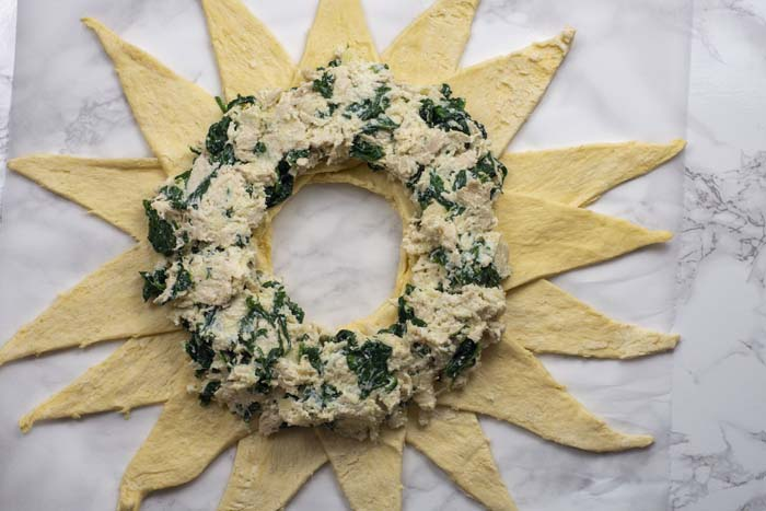 Crescent rolls laid out in a star shape on a piece of parchment paper with chicken and spinach mixture on the inside over a white and grey marble surface