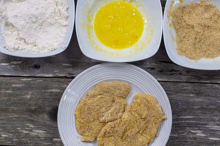 Round white plate with breaded chicken in front of white bowls with flour, egg, and bread crumbs all on a wooden surface