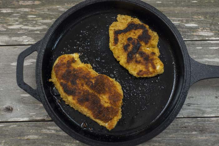 Cast iron skillet with two breaded and fried chicken breasts on a wooden surface