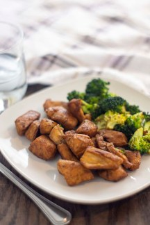 Dijon chicken and broccoli on a square white plate next to a stainless steel fork with a glass of water and a white and brown towel behind the plate all on a wooden surface (vertical)