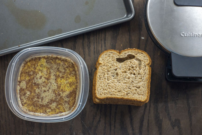 Small container of egg, milk, and cinnamon mixture next to a stack of sliced bread with a waffle iron and metal baking sheet behind all on a wooden surface