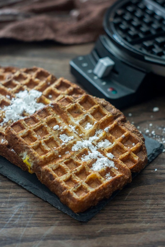 Pieces of French Toast Waffles sprinkled with powdered sugar at a diagonal on a slate tray with a waffle iron behind all on a wooden surface (vertical)