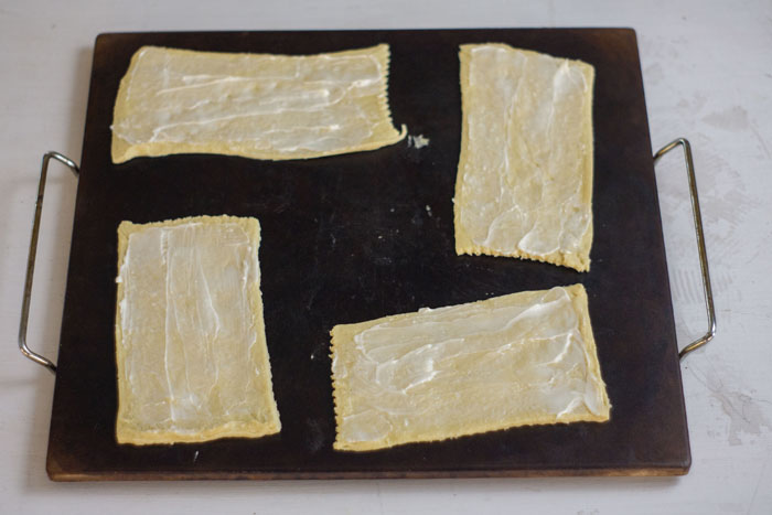 Baking stone with rectangular crescent rolls covered in butter on top on a white and grey surface