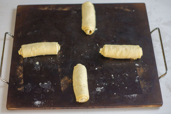 Baking stone with rolled up crescent rolls on a white and grey surface