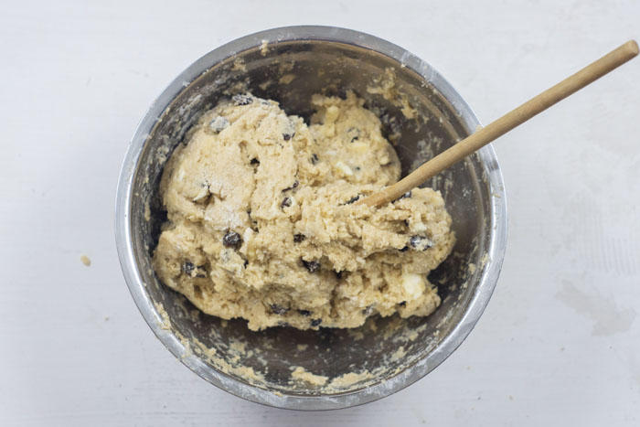 Rock cake dough with a wooden spoon in a stainless steel bowl on a white surface