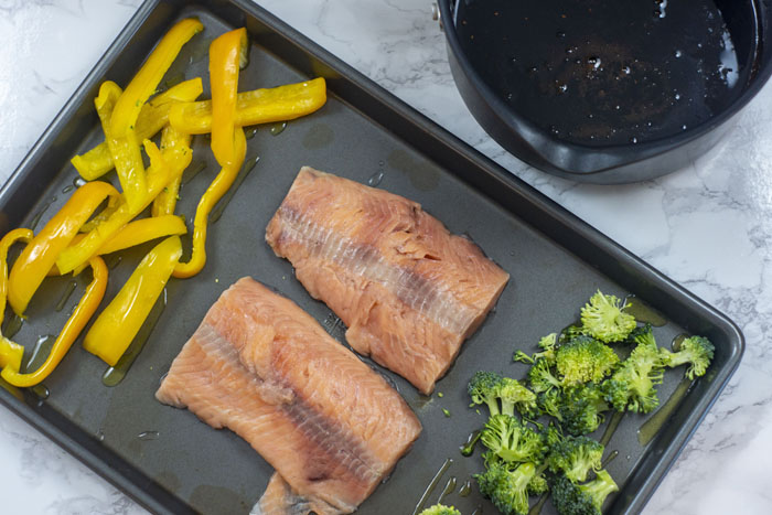 Metal sheet pan with two salmon fillets in the center surrounded by sliced yellow pepper and chopped broccoli all drizzled with olive oil next to a medium sauce pot of soy-molasses glaze all on a white and grey marble surface
