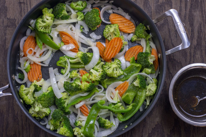 Skillet with sauteed broccoli, onion, green pepper, carrots, and garlic next to a stainless steel bowl of soy sauce mixture all on a wooden surface