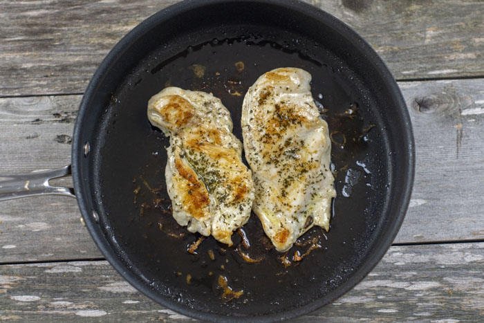 Cooked chicken breast topped with seasonings in a large nonstick skillet over a wooden surface
