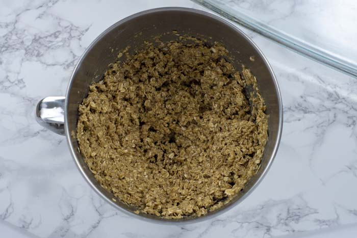 Oats and oat flour mixed with honey and coconut oil in a stainless steel bowl next to a glass baking dish on a white and grey marble surface