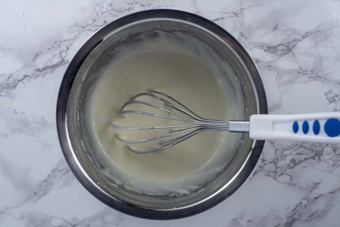 Stainless steel mixing bowl with glaze and a whisk on a white and grey marble surface