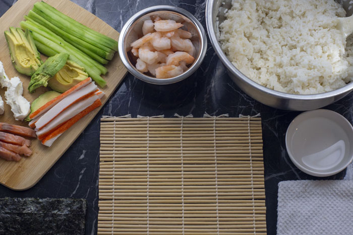 Sushi setup with sliced ingredients on a bamboo cutting board next to a white bowl of shrimp and another bowl of sushi rice with a bowl of water and a white towel and a pile of seaweed surrounding a bamboo mat all on a black and white marble surface