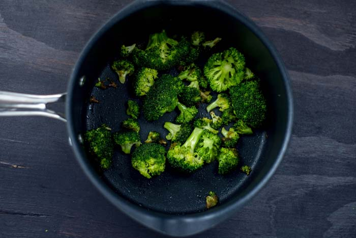 Roasted broccoli in a medium saucepan on a wooden surface