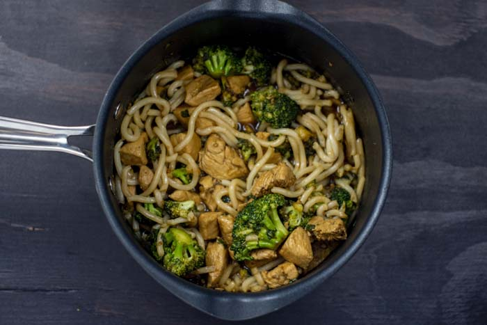 Teriyaki chicken with broccoli and udon noodles in a medium saucepan on a wooden surface