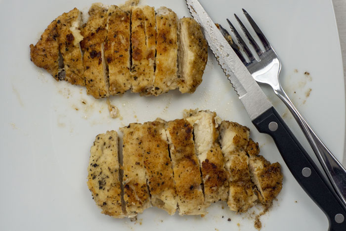 Sliced cooked chicken on a white plate with a fork and knife
