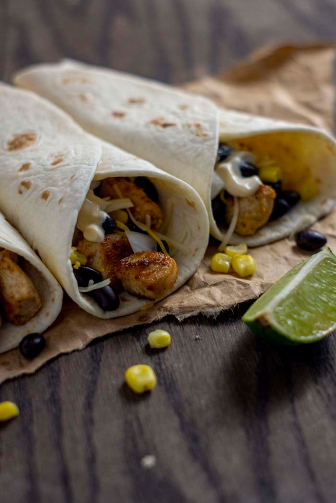 Three chipotle chicken tacos with a few ingredients falling out on a piece of brown parchment paper next to a lime wedge on a wooden surface (vertical)