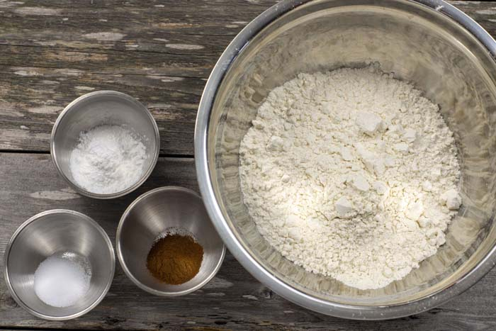 Stainless steel bowls with flour, sugar, cinnamon, and baking powder on a wooden surface