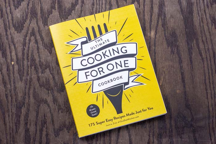 Cover of The Ultimate Cooking For One Cookbook on a wooden surface