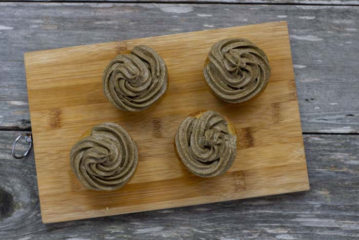 Four cupcakes with piped brown buttercream frosting on top on a bamboo board on a wooden surface