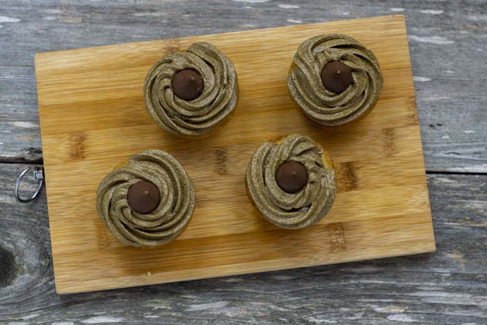 Four cupcakes with piped brown buttercream frosting topped with a Hershey's kiss on each on a bamboo board on a wooden surface