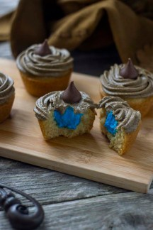 Sorting hat cupcakes with one cut in half showing blue frosting inside on a bamboo board with the sorting hat behind and a magic wand in front all on a wooden surface (vertical)
