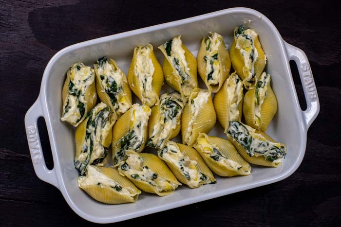 Pasta shells stuffed with spinach and artichoke mixture in a line in a white casserole dish on a wooden surface
