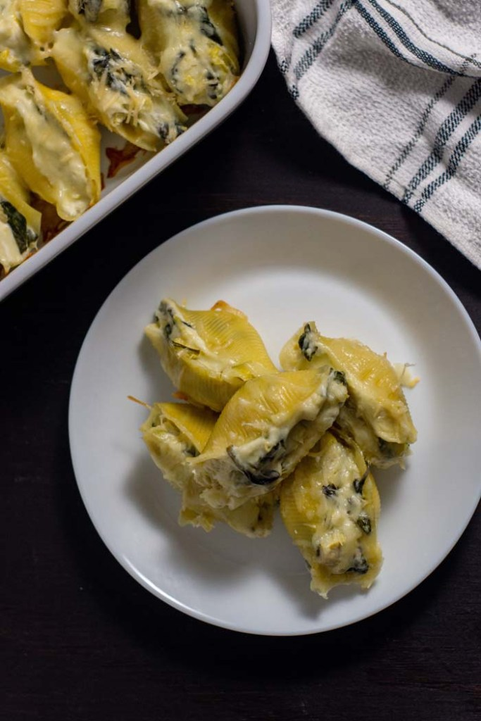 Five spinach and artichoke stuffed shells piled on a round white plate next to a white casserole dish with more shells and a white and blue towel behind all on a wooden surface (vertical)