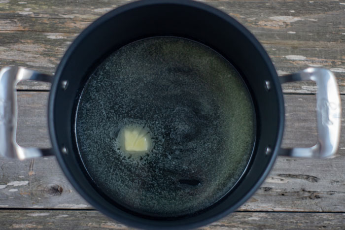 Butter almost completely melted in a large black stockpot on a wooden surface
