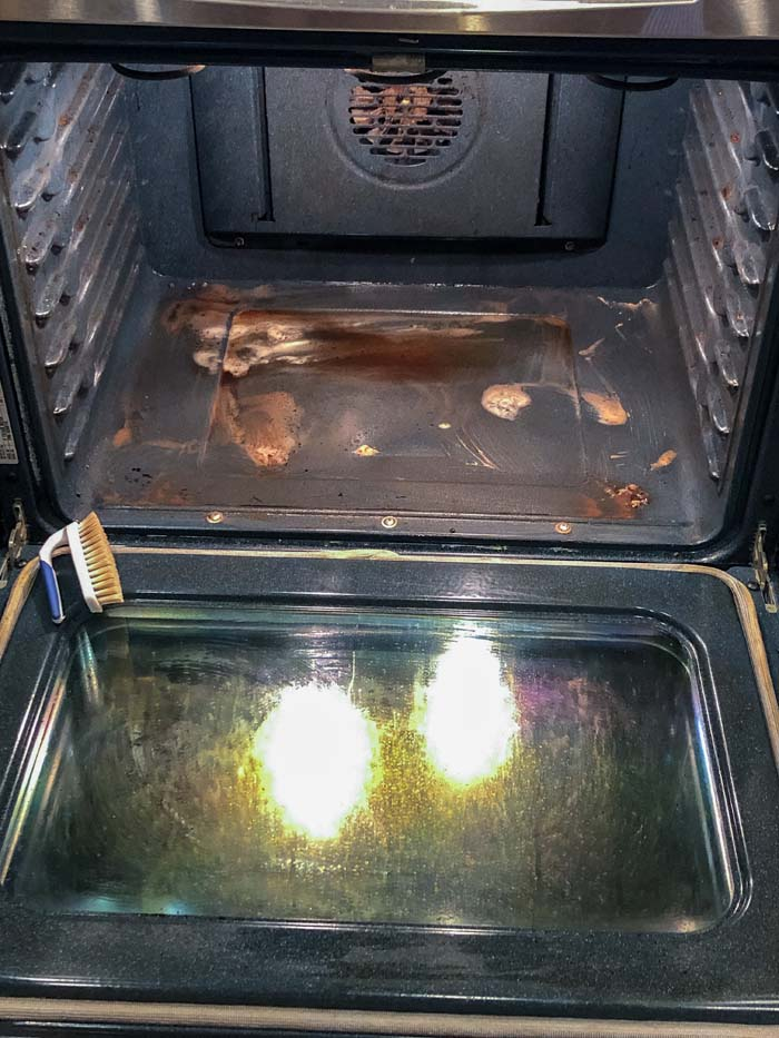 Oven with dirty baking soda mixture and a scrubber