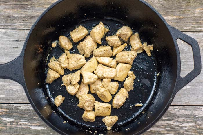 Diced chicken in a cast-iron pan over a wooden surface