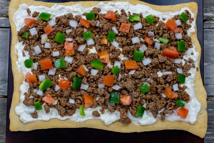 Baked pizza crust with cream cheese and sour cream mixture spread to the edges topped with prepared taco meat, chopped onions, chopped tomatoes, and chopped green bell pepper sitting on a baking stone on a wooden surface