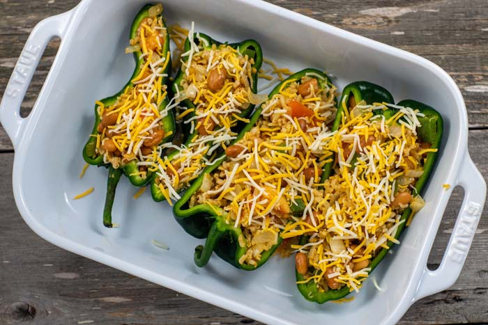 Two poblano peppers cut in half filled with taco filling in a white casserole dish on a wooden surface