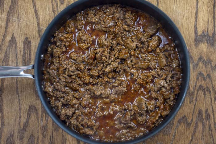 Ground beef with taco seasoning and water in a large skillet on a wooden surface