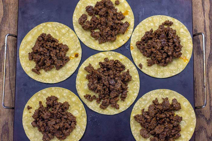 6 corn tortillas topped with a scoop of prepared taco meat on a baking stone on a wooden surface