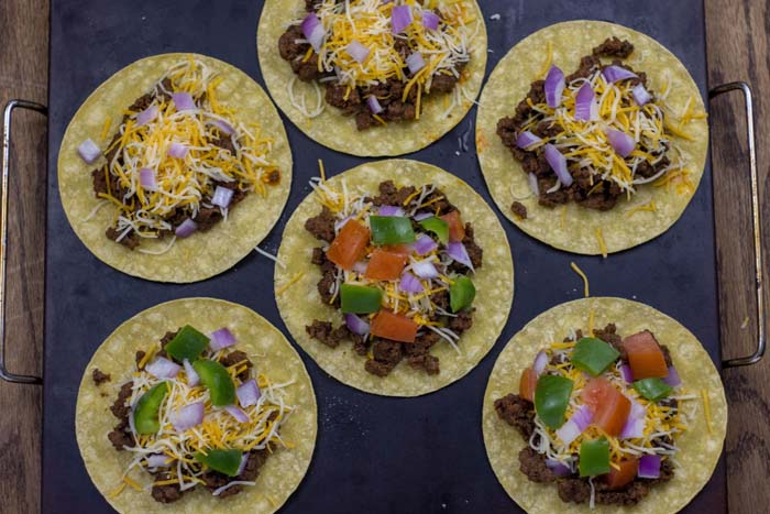 6 corn tortillas topped with a scoop of prepared taco meat, shredded cheese, and taco toppings on a baking stone on a wooden surface