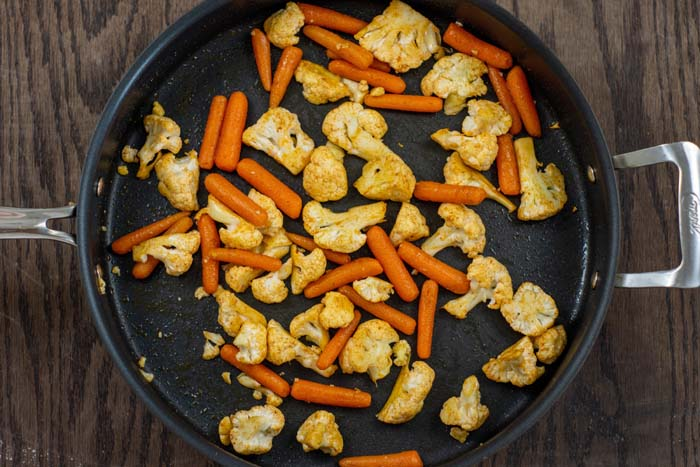 Chopped cauliflower and baby carrots in a large nonstick skillet on a wooden surface