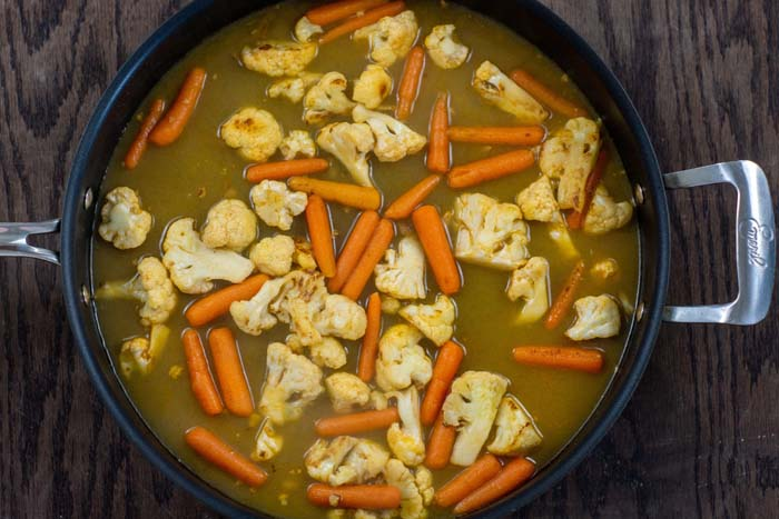 Chopped cauliflower and baby carrots with broth in a large nonstick skillet on a wooden surface