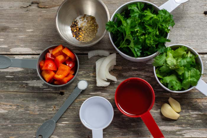 Ingredients for green chimichurri sauce in measuring cups on a wooden surface