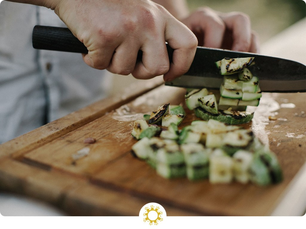 Woman's hand using a chef's knife to chop a green vegetable on a bamboo cutting board (with logo overlay)