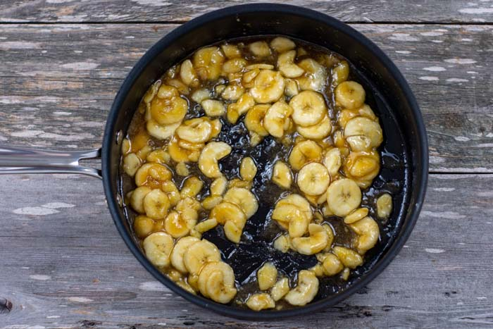 Bananas foster filling in a large skillet on a wooden surface