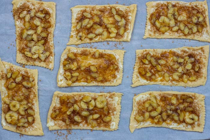 Flattened crescent rolls covered with butter and bananas foster filling on parchment paper