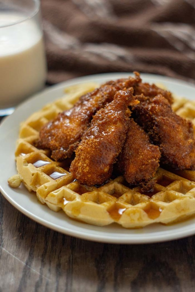 Fried chicken on top of a waffle covered with syrup on a round white plate with a glass of milk and a brown and white towel behind the plate all on a wooden surface (vertical)