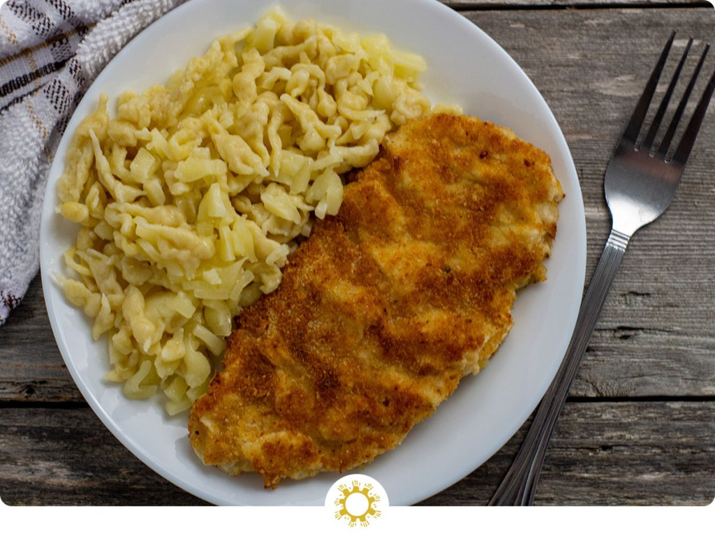 Chicken schnitzel next to cheesy spaetzle on a round white plate with a white and brown towel behind all on a wooden surface (with logo overlay)