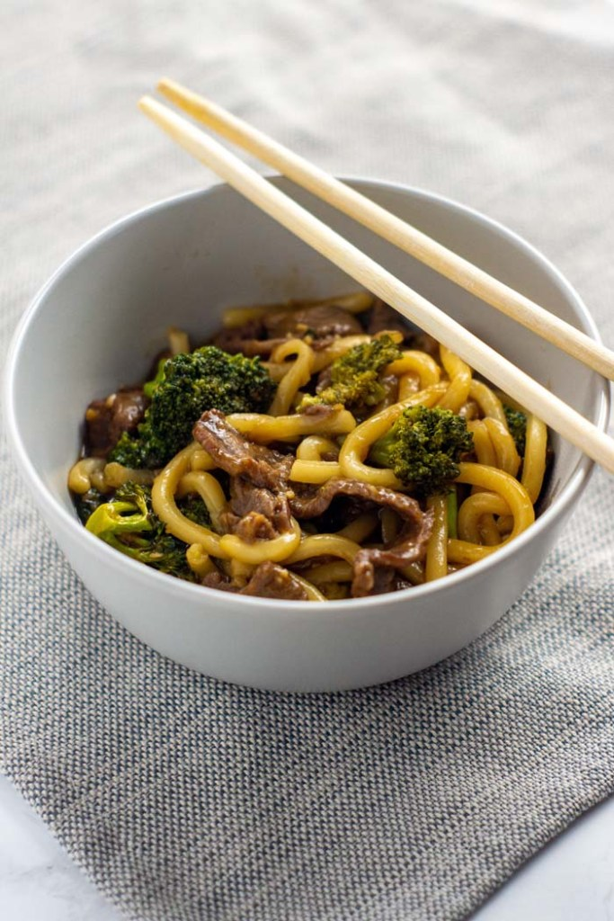 Beef and broccoli with udon noodles in a round white bowl with wooden chopsticks on a grey placemat all on a white surface (vertical)