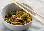 Beef and broccoli with udon noodles in a round white bowl with wooden chopsticks on a grey placemat all on a white surface