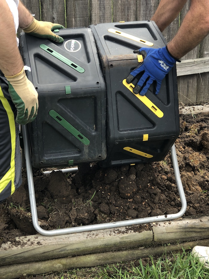 Double compost bin being emptied into a raised garden bed